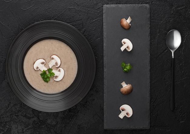 黒の石板と新鮮なキノコと黒の背景にクリーミーな栗のシャンピニオンマッシュルームスープの黒のレストランプレート。上面図。
