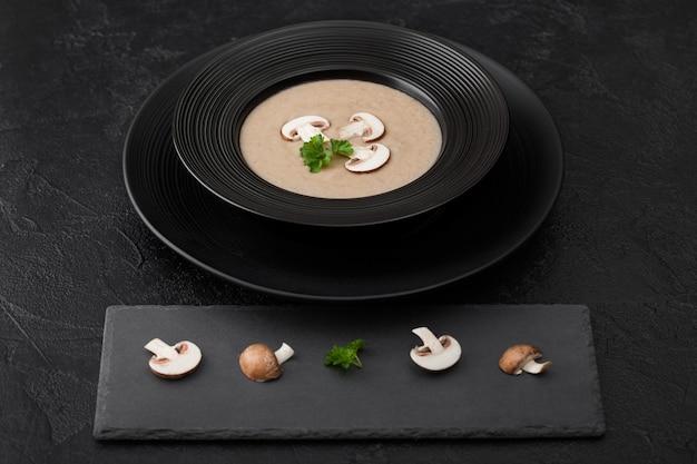黒の石板と新鮮なキノコと黒の背景にクリーミーな栗のシャンピニオンマッシュルームスープの黒のレストランプレート。