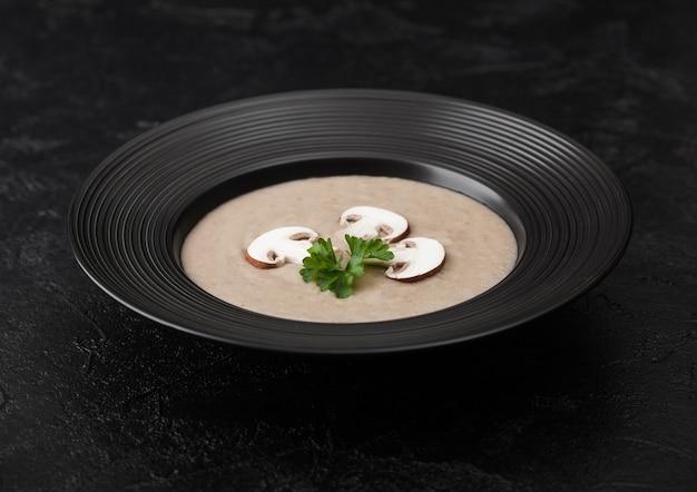 黒の背景にクリーミーな栗のシャンピニオンマッシュルームスープの黒のレストランプレート。