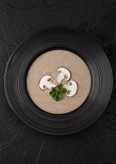 黒のクリーム色の栗シャンピニオンキノコスープの黒レストランプレート。上面図。