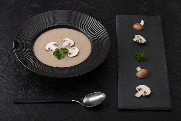 黒い石の板と新鮮なキノコと黒のクリーミーな栗シャンピニオンキノコスープの黒レストランプレート。上面図。
