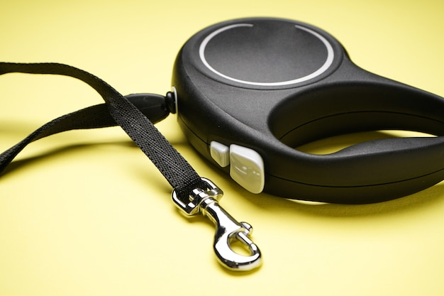 Black retractable dog leash on a yellow background. close-up.