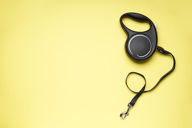 Black retractable dog leash on a yellow background, space for text. flat lay.
