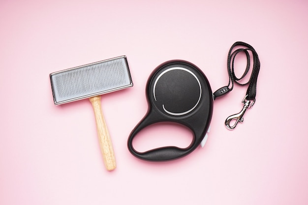 Black retractable leash and brush for dogs on a pink background, flat lay.