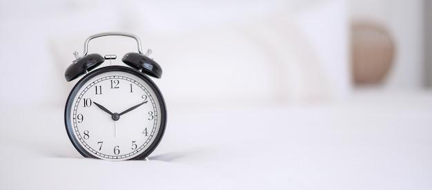 Black retro alarm clock on bed at night Premium Photo