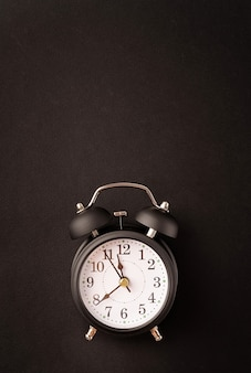 Black retro alarm clock isolated on black background with copy space