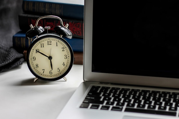 Black retro alarm clock and laptop with books on a dark background