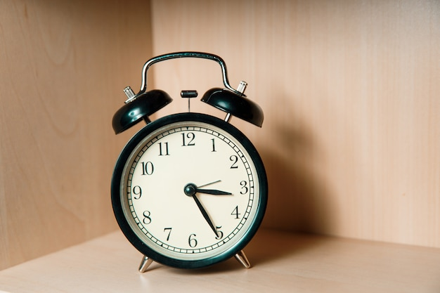 Black retro alarm clock stands on a light wooden shelf. classic alarm clock.