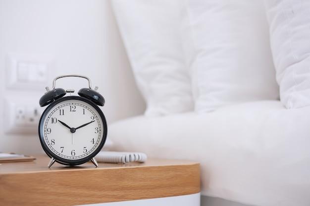 Black retro alarm clock on table in bedroom at night
