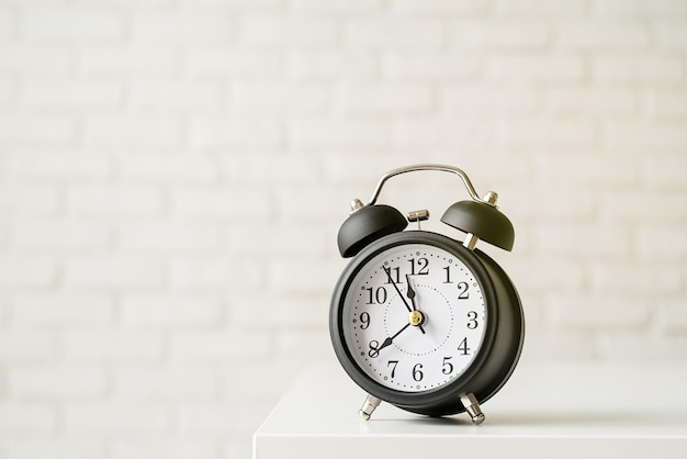 Black retro alarm clock on white brick wall background with copy space
