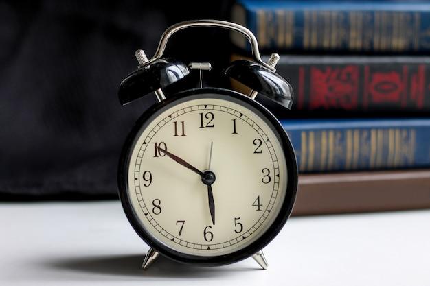 Black retro alarm clock with books on a dark background