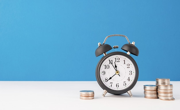 Black retro alarm clock with coins on blue background