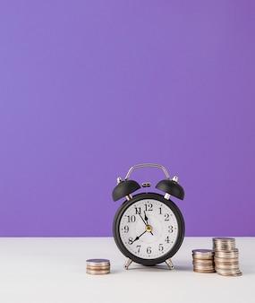 Black retro alarm clock with coins on purple background