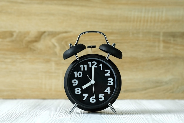 Black retro alarm clock on wood table