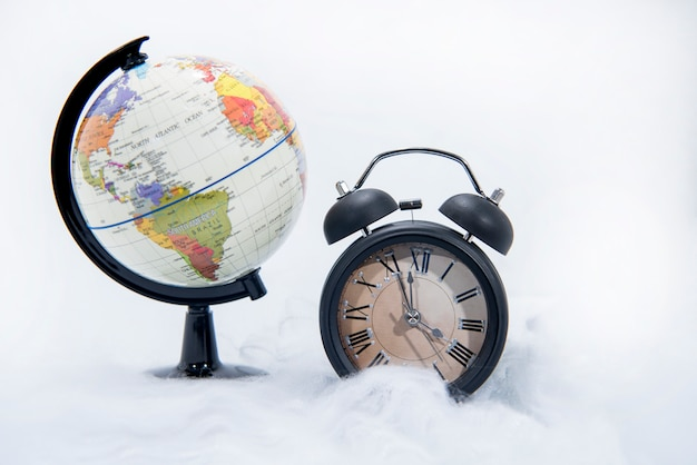 Black retro alarm clock and world globe
