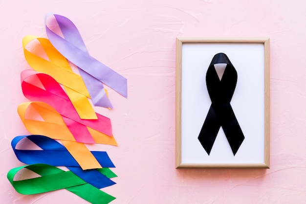 Black ribbon on white wooden frame near the row of colorful awareness ribbon