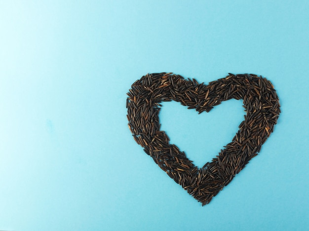 Black rice heart on blue paper background top view