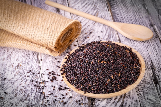 The black rice on old wooden table. selective focus