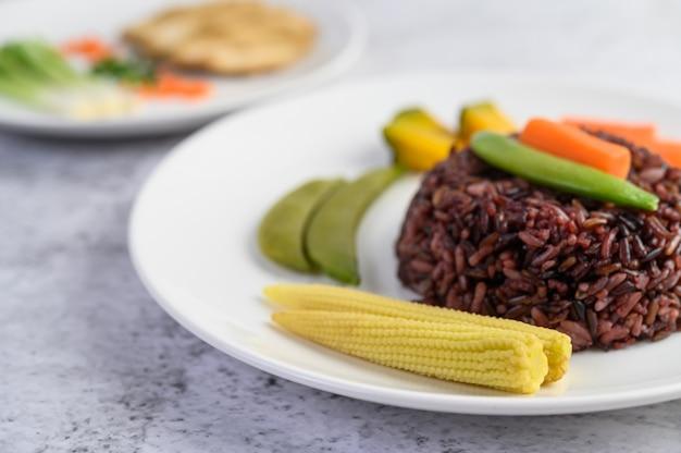 호박, 완두콩, 당근, 아기 옥수수와 함께 접시에 검은 쌀
