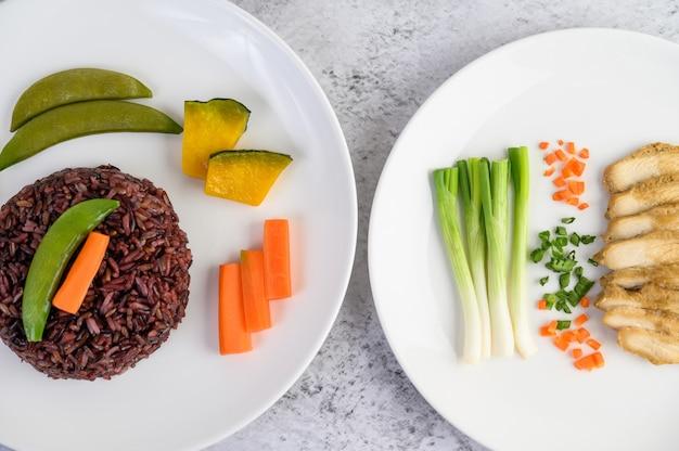 Riso nero su un piatto con zucca, piselli, carote, mais e petto di pollo al vapore.