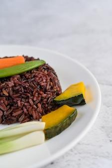 Riso nero su un piatto con zucca, piselli, carote, mais per bambini
