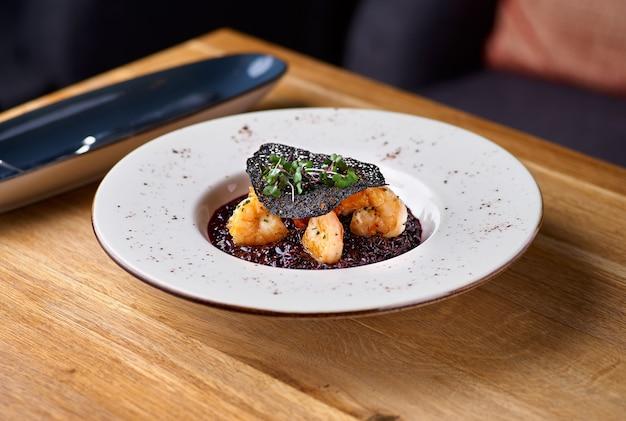 Ризотто с черным рисом. ризотто с креветками на белой тарелке на столе, в ресторане