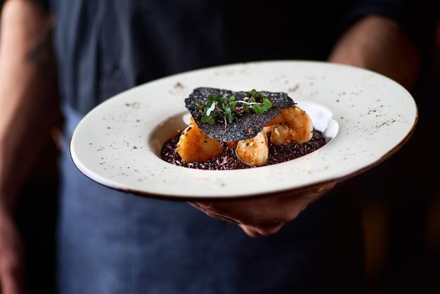 Ризотто с черным рисом. ризотто с креветками на белой тарелке на столе