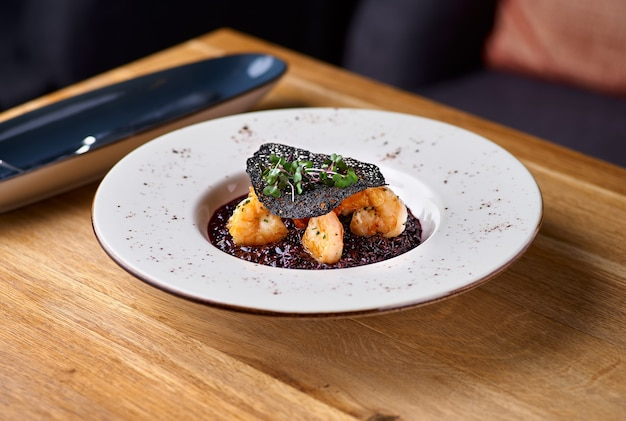 Black rice risotto. shrimp risotto on a white plate on the table, serving in a restaurant
