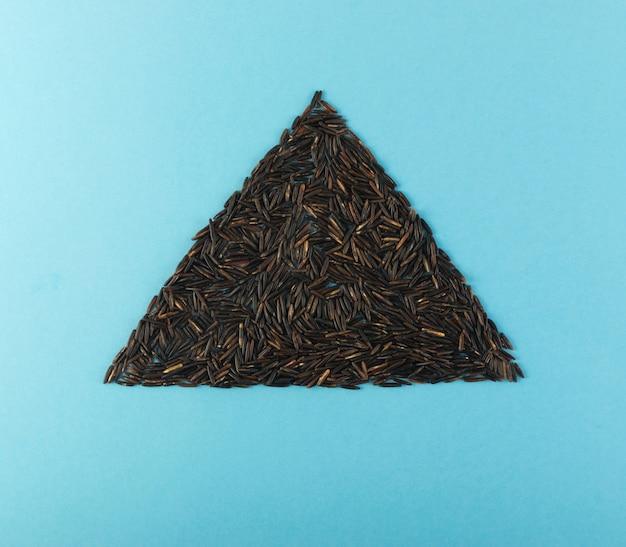 Треугольник черного риса на синем фоне
