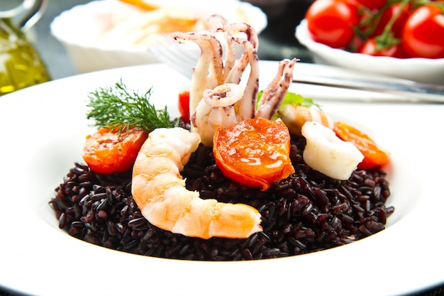 Black rice with sliced squids ,prawns and tomato on white plate