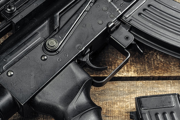 Черная винтовка ак-47 на деревянной доске крупным планом
