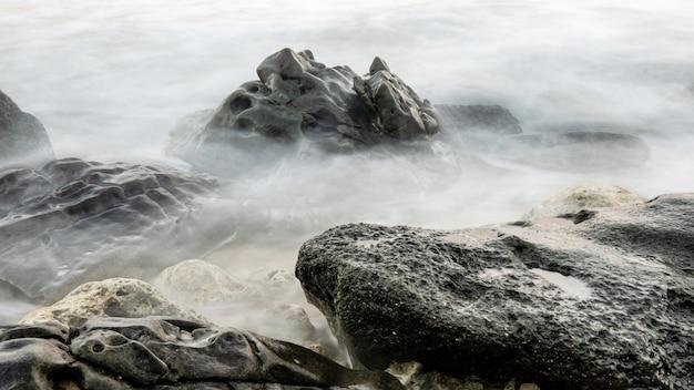 Черная горная порода около водоема во время дневной картины природы