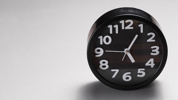 Black round alarm clock on gray background