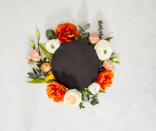 아름다운 꽃, 잎, 복사 공간이 있는 검은색 원형 카드. 휴일 인사말