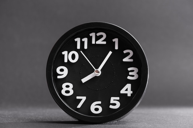 Black round clock against gray background