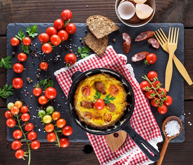 Black round frying pan with fried omelette