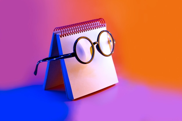 Black round glasses lie on a notepad in neon light on pink background