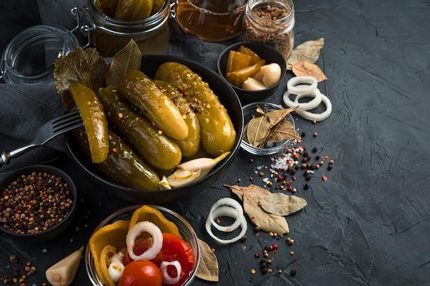 Черная круглая тарелка с маринованными огурцами, специями и лавровым листом на темном фоне. концепция домашних солений.