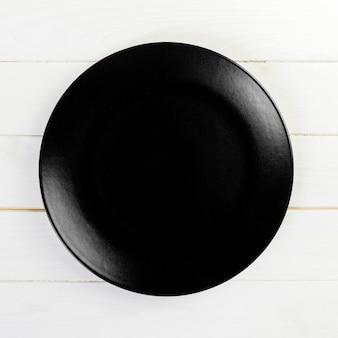 Black round plate on wood
