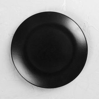 Black round plate on wooden background, top view, copy space
