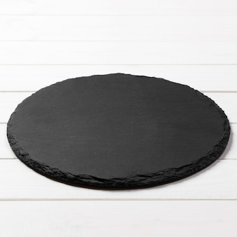 Black round plate on wooden , top view, copy space