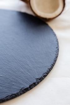 Черная круглая каменная тарелка с кокосовым крупным планом