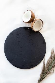 Черная круглая каменная тарелка с кокосом. вид сверху.