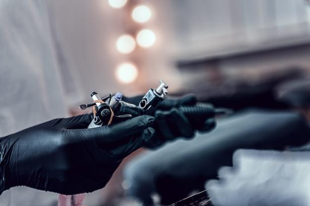검은 색 고무 장갑. 살롱에서 작업을 위해 장비를 준비하는 내부 잉크로 특수 장치를 사용하는 문신 마스터