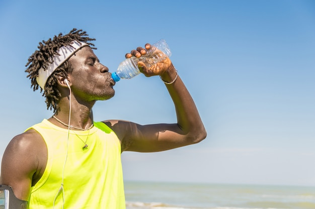 Black runner taking rest drinking energy drink at the beach at summer