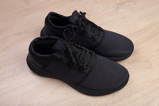 Black running shoes on wooden