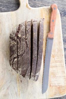 まな板の上でナイフで切った黒ライ麦パン、伝統的な食べ物のクローズアップ