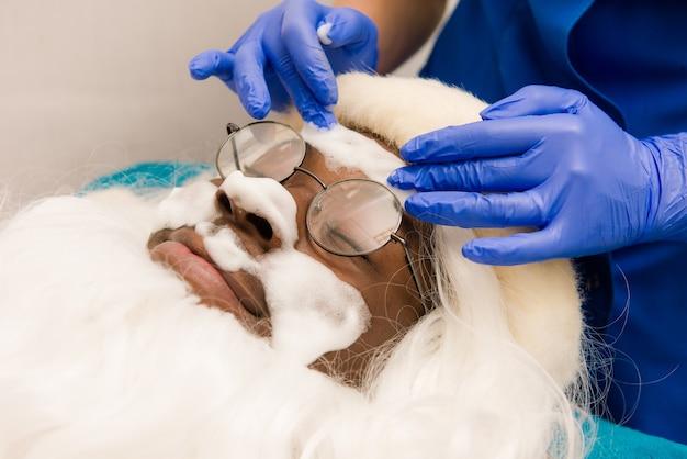 Black santa claus in beauty spa. spa facial mask application.