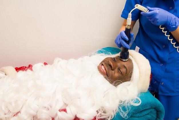 Black santa claus doing cosmetic procedures in spa clinic. cosmetic procedures in spa clinic.