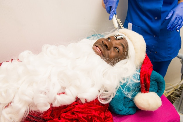 Black santa claus doing cosmetic procedures in spa clinic.